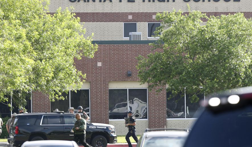 FILE - In this May 18, 2018, file photo, law enforcement officers respond to Santa Fe High School after an active shooter was reported on campus in Santa Fe, Texas. Nearly a month after the worst Texas public school shooting in history, state lawmakers meet Monday, June 11, 2018, for the first time since the Santa Fe High School shooting that left 10 people dead. (Steve Gonzales/Houston Chronicle via AP, File)