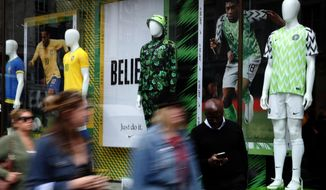 In this June 5, 2018 photo people walk by Nigerian and Brazil national soccer team jerseys which are on display at a shop in London. With just days to go before the FIFA World Cup, some winners and losers have emerged among the often wild and wacky team jerseys. (AP Photo/Frank Augstein)