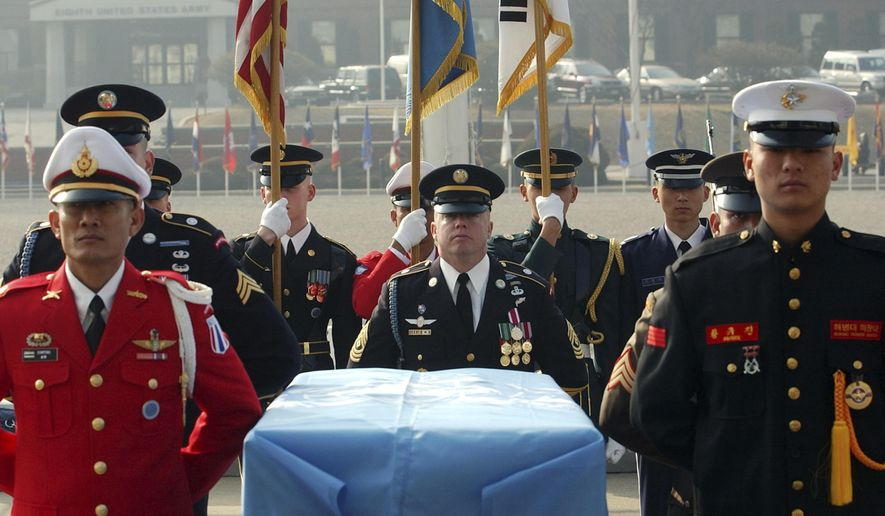 FILE - In this Friday, Feb. 14, 2003, United Nations Command soldiers stand around the coffin of one Korean War-era remains during an honor guard departure ceremony, at Yongsan U.S. Army Base in Seoul, South Korea. The most tangible outcome of the summit between President Donald Trump and North Korean leader Kim Jong Un seems to be a commitment to recover the remains of U.S. military personnel missing in action and presumed dead from the Korean War. (AP Photo/Yun Jai-hyoung, File)