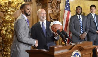 Pennsylvania Gov. Tom Wolf shows off an autographed basketball presented to him by Phil Booth and three other members of Villanova's championship-winning men's basketball team, Tuesday, June 12, 2018 in Harrisburg, Pa. (AP Photo/Marc Levy)
