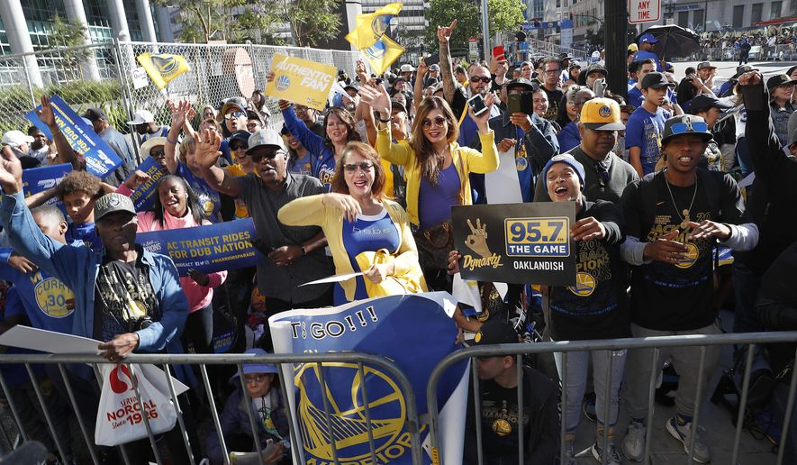 Fans wait for the parade to start in honor of the Golden State Warriors, Tuesday, June 12, 2018, in Oakland, Calif., to celebrate the team's NBA basketball championship. (AP Photo/Tony Avelar)