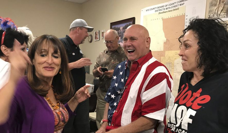 "In this Tuesday, June 12, 2018 photo Nevada brothel owner Dennis Hof, second from right celebrates after winning the primary election in Pahrump, Nev. Hof, the owner of half a dozen legal brothels in Nevada and star of the HBO adult reality series ""Cathouse,"" won a Republican primary for the state Legislature on Tuesday, ousting a three-term lawmaker. At right is former madam and reality TV personality Heidi Fleiss.  (David Montero /Los Angeles Times via AP)"