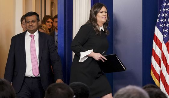 White House press secretary Sarah Huckabee Sanders, right, accompanied by White House principal deputy press secretary Raj Shah, left, arrives to speak to the media during the daily press briefing at the White House, Tuesday, March 27, 2018, in Washington. Sanders discussed the removal of Russian diplomats, the opiate crisis, and other topics. (AP Photo/Andrew Harnik)