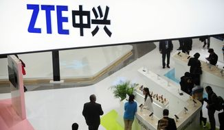 In this Wednesday, Feb. 26, 2014, file photo, people gather at the ZTE booth at the Mobile World Congress, the world's largest mobile phone trade show in Barcelona, Spain. (AP Photo/Manu Fernandez, File)