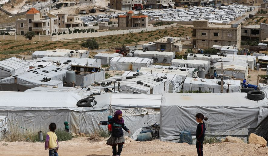 Syrian refugee children play at an informal refugee camp, which is seen set between the houses and buildings in Arsal, near the border with Syria, east Lebanon, Wednesday, June 13, 2018. A public spat between the Lebanese government and the United Nation's refugee agency deepened Wednesday as Lebanon's caretaker foreign minister kept up his criticism, accusing the agency of discouraging Syrian refugees from returning home. Lebanon is home to more than a million Syrian refugees, or about a quarter of the country's population, putting a huge strain on the economy. (AP Photo/Hussein Malla)