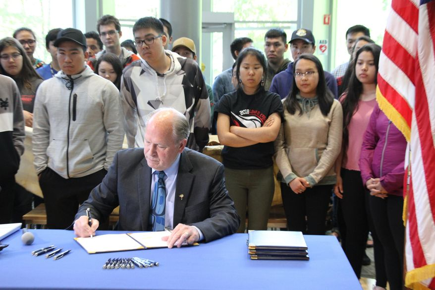 Alaska Gov. Bill Walker signs state spending bills during a ceremony Wednesday, June 13, 2018, at the University of Alaska Anchorage. Walker did perform some line-item vetoes, including rejecting funding for a bridge project that would link Anchorage to the Matanuska-Susitna Borough and a Vitamin D deficiency study. (AP Photo/Mark Thiessen).