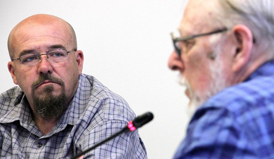 Nicholas Miller, left, listens as fellow Alaska Marijuana Control Board member Loren Jones addresses officials form the tax division during a board meeting Wednesday, June 13, 2018, in Anchorage, Alaska. The board discussed possible changes to how marijuana is taxed, a decision that ultimately would have to be made by the Alaska Legislature. (AP Photo/Mark Thiessen)