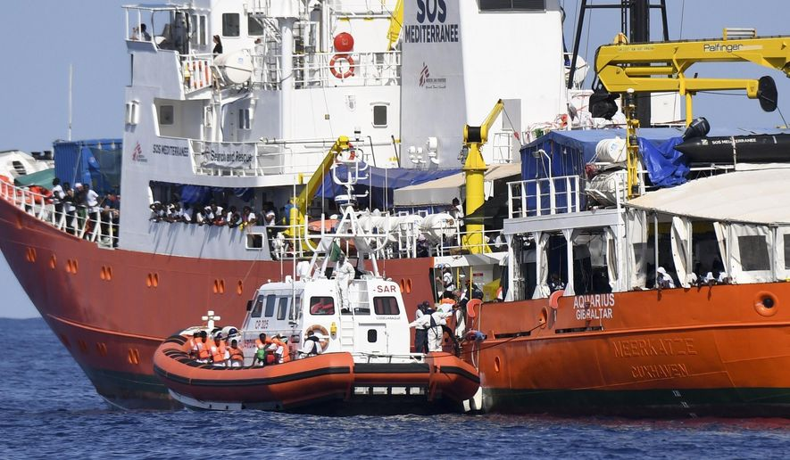 """An Italian Coast Guard boat approaches the French NGO """"SOS Mediterranee"""" Aquarius ship as migrants are being transferred, in the Mediterranean Sea, Tuesday, June 12, 2018. Italy dispatched two ships Tuesday to help take 629 migrants stuck off its shores on the days-long voyage to Spain in what is forecast to be bad weather, after the new populist government refused them safe port in a dramatic bid to force Europe to share the burden of unrelenting arrivals. (AP Photo/Salvatore Cavalli)"""