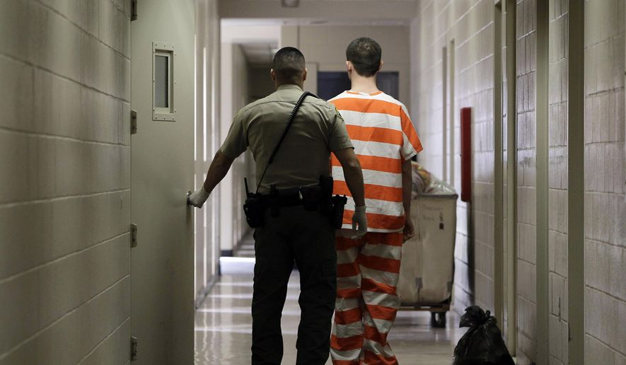 FILE - In this Feb. 21, 2013 file photo, an inmate at the Madera County Jail is taken to a housing unit at the facility in Madera, Calif. Independent researchers say that California voters' decision to reduce penalties for drug and property crimes in 2014 led to a jump in thefts, particularly car burglaries and shoplifting. The Public Policy Institute of California reported Tuesday, June 12, 2018 that larcenies increased about 9 percent from 2014 to 2016. Thefts from motor vehicles accounted for about three-quarters of the increase. San Francisco alone recorded more than 30,000 auto burglaries in 2017. (AP Photo/Rich Pedroncelli, File)