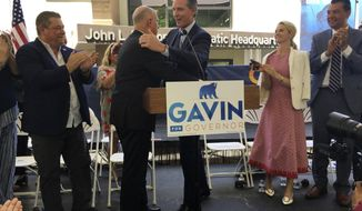 Gov. Jerry Brown, center left, hugs Lt. Gov. Gavin Newsom at a unity rally at state Democratic headquarters in Sacramento, Calif. on Wednesday, June 13, 2018. Brown endorsed Newsom in the race to replace him as governor. (AP Photo/Jonathan J. Cooper)