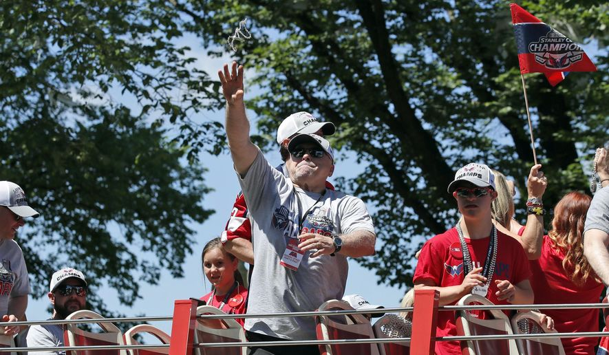 Washington Capitals coach Barry Trotz tosses a strand of beads during a victory parade for the NHL hockey Stanley Cup champions Tuesday, June 12, 2018, in Washington. (AP Photo/Alex Brandon, Pool)