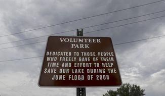 This June 6, 2018 photo shows a sign in Volunteer Park in Pardeeville, Wis. Flood memories are still vivid but for some the 2008 event has provided new opportunity. (Steve Apps/Wisconsin State Journal via AP)