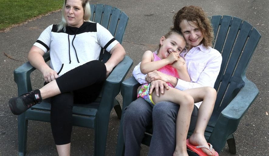 In this May 31, 2018 photo, neighbors Hillary Harris, left, Dawn Johnson, Harris' daughter, Stella, sit outside in Eau Claire, Wis. The neighbors recently discovered they are sisters. Since that time, Harris' daughter, Stella, has formed a strong bond with her new aunt Dawn. (Dan Reiland/The Eau Claire Leader-Telegram via AP)
