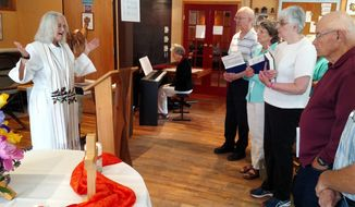 Kathy Redig, founder and pastor of the All Are One Roman Catholic Church, in Winona, Minn., says Mass in the Lutheran Campus Center on Huff Street. Redig and the church will be celebrating their 10-year anniversary Sunday, June 10, 2018.   (Tesla Mitchell /The Winona Daily News via AP)