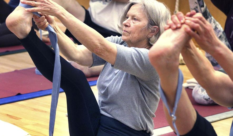 Lynne Valiquette works through exercises during an advanced yoga class April 10, 2018 at The Yoga Place in La Crosse, Wis. (Peter Thomson/La Crosse Tribune via AP)
