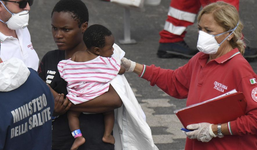 "A migrant woman and baby wait for a health check up after disembarking from Italian Coast Guard vessell ""Diciotti"" which docked at the Sicilian port of Catania, southern Italy, Wednesday, June 13, 2018. The vessel docked in Catania with 932 migrants aboard in a sign that Italy under the populist 5-Star Movement and anti-migrant League is still accepting some migrants, but is forcing other countries to share the burden. (AP Photo/Salvatore Cavalli)"