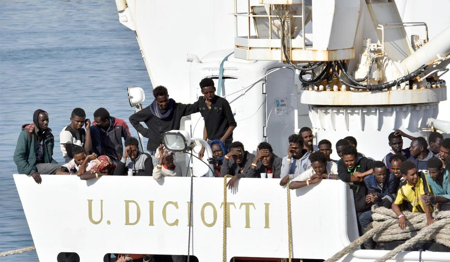 "Migrants wait to disembark from an Italian Coast Guard vessell ""Diciotti"" as it docks at the Sicilian port of Catania, southern Italy, Wednesday, June 13, 2018. The vessel docked in Catania with 932 migrants aboard in a sign that Italy under the populist 5-Star Movement and anti-migrant League is still accepting some migrants, but is forcing other countries to share the burden.  (Orietta Scardino/ANSA via AP)"