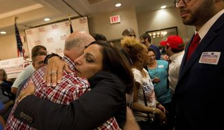 State Rep. Katie Arrington hugs supporters as she defeated U.S. Rep. Mark Sanford at the DoubleTree by Hilton Hotel for Katie Arrington's results party on Tuesday, June 12, 2018, in North Charleston, S.C.  (Andrew Whitaker/The Post And Courier via AP)