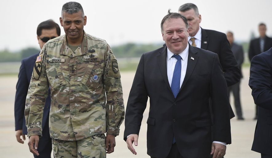 U.S. Secretary of State Mike Pompeo, right, walks with U.S. Gen. Vincent K. Brooks, left, commander of United States Forces Korea, upon his arrival at Osan Air Base in Pyeongtaek, Wednesday, June 13, 2018.  South Korea's presidential office said Pompeo will meet President Moon Jae-in Thursday morning to discuss the meeting, which made history as the first between sitting leaders of the U.S. and North Korea. (Jung Yeon-je/Pool Photo via AP)