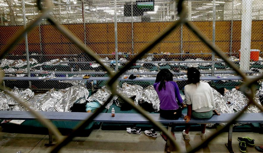 FILE - In this Wednesday, June 18, 2014, file photo, two young girls watch a World Cup soccer match on a television from their holding area where hundreds of mostly Central American immigrant children are being processed and held at the U.S. Customs and Border Protection Nogales Placement Center in Nogales, Ariz. As of Thursday, July 17, 2014, immigrant children caught crossing the Mexican border into Texas illegally and alone are no longer being sent to a massive Nogales facility. (AP Photo/Ross D. Franklin, Pool, File)