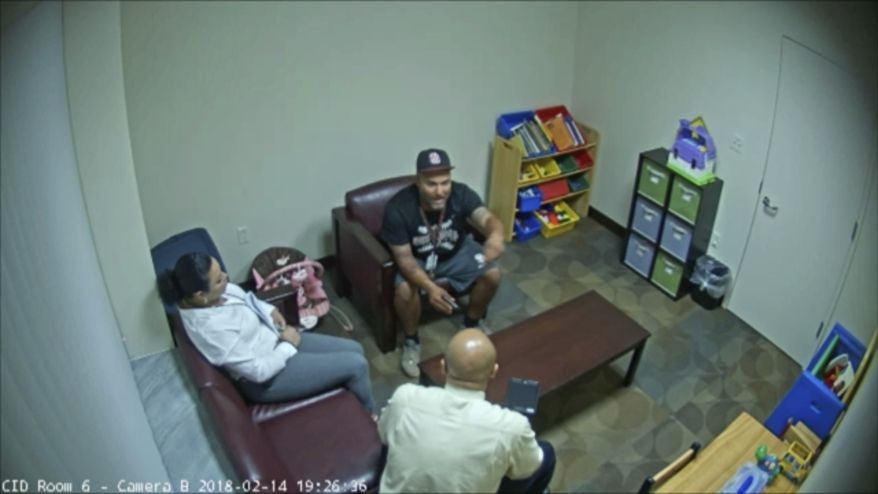 In this Feb. 14, 2018 frame from surveillance video provided by the Broward Sheriff's Office, Andrew Medina, center, is interviewed by detectives following the shooting at Marjory Stoneman Douglas High School in Florida. Medina, a baseball coach and unarmed campus monitor, told detectives he watched Nikolas Cruz get out of an Uber and head straight to the building where 17 people would be killed moments later at the school. (Broward Sheriff's Office via AP)