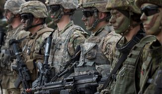 NATO soldiers of U.S. and Lithuania, right, take part in a military exercise 'Saber Strike 2018' at the Training Range in Pabrade some 60km (38 miles) north of the capital Vilnius, Lithuania, Monday, June 11, 2018. A major U.S.-led military exercise with 18,000 soldiers from 19 primarily NATO countries is taking place in the alliance's eastern flank involving Poland and the three Baltic states of Estonia, Latvia, Lithuania. (AP Photo/Mindaugas Kulbis)