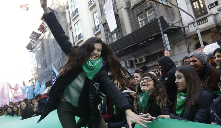 Women celebrate the approval of a bill legalizing abortion by the lower house of congress, in Buenos Aires, Thursday, June 14, 2018. The lower house of Argentina's congress has approved a bill that would legalize elective abortion in the first 14 weeks of pregnancy, sending the measure to the Senate. President Mauricio Macri has said he'll sign the bill if it's approved. (AP Photo/Jorge Saenz)