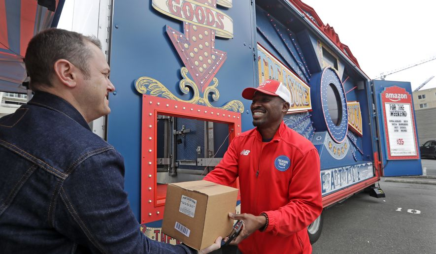 In this May 24, 2018, photo Amazon worker Khayyam Kain, right, hands off a package to a customer at an Amazon Treasure Truck in Seattle. The Treasure Truck is a quirky way for the online retailer to connect with shoppers in person, expand its physical presence and promote itself. Amazon has also used the trucks to try to bring people into Whole Foods, the grocery chain it bought last year. The trucks debuted two years ago and now roam nearly dozens of cities in the United States and England. (AP Photo/Elaine Thompson)