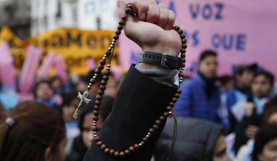 Pro-life protesters rally against a proposed law to legalize abortion, with one holding a Catholic rosary, near Congress in Buenos Aires, Wednesday, June 13, 2018. Argentina's legislature has begun debating a measure that would allow elective abortions in the first 14 weeks of gestation. (AP Photo/Jorge Saenz)