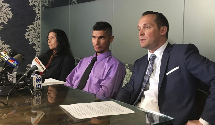 Jose Conde, center, listens to news media while seated between his mother, Rosa Conde, and attorney Bret Royle at Royle's office in Phoenix on Thursday, June 14, 2018. Recently released Mesa police videos show officers punching Conde, who was unarmed, and later mocking him while was lying on a hospital room floor after his Jan. 28 arrest. (AP Photo/Terry Tang)