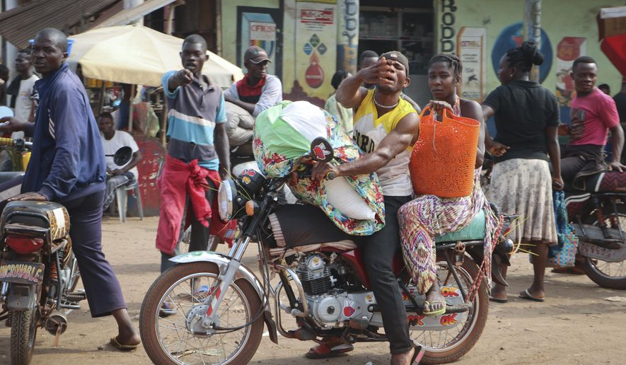 In this photo taken Saturday, June 2, 2018, a motorcycle taxi driver carries a passenger through the streets of Mbandaka, Congo. Hundreds are being vaccinated in Congo's deadly Ebola outbreak, but busy taxi drivers who might be ferrying the sick in an infected city of more than 1 million argue they are on the front lines as well and should receive the vaccine. (AP Photo/Sam Mednick)