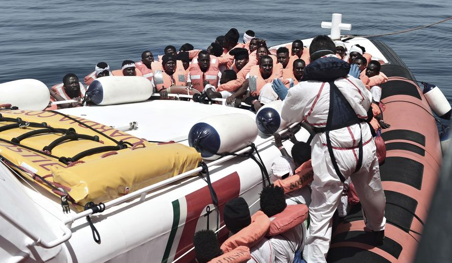 """This June 12, 2018 photo released Wednesday, June 13, 2018 by French NGO """"SOS Mediterranee"""" shows migrants being transferred from the Aquarius ship to Italian Coast Guard boats, in the Mediterranean Sea. Italy dispatched two ships Tuesday to help take 629 migrants stuck off its shores on the days-long voyage to Spain in what is forecast to be bad weather, after the new populist government refused them safe port in a dramatic bid to force Europe to share the burden of unrelenting arrivals. (Kenny Karpov/SOS Mediterranee via AP)"""