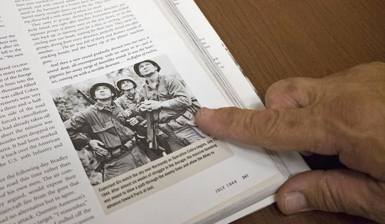 """In this May 25, 2018 photo, Bill Henson points out a photo of his father, William Henson, taking during Operation Cobra in World War II in the book companion to Ken Burns'  documentary """"The War, in Carbondale, Ill. Henson said this photo has popped up multiple times and, especially since his father's death in 2010, has been a nice surprise every time. Henson said he sees the ghost of his father in a lot of places, in books, on television and even on the internet. This is because his father, served as a staff sergeant in one of the most iconic Army groups that served in World War II, the 4th Infantry Division, 8th Battalion.(Isaac Smith/The Southern, via AP)"""