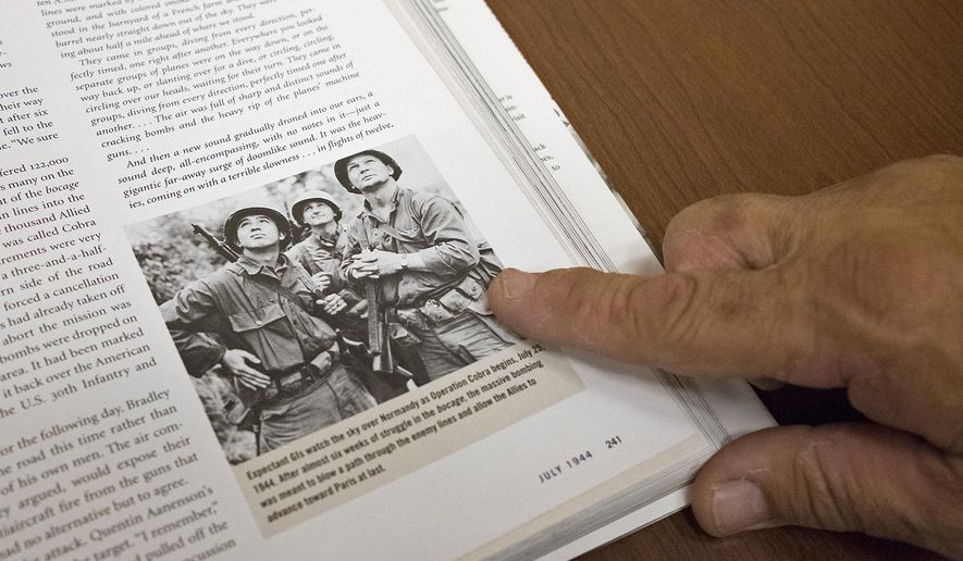 "In this May 25, 2018 photo, Bill Henson points out a photo of his father, William Henson, taking during Operation Cobra in World War II in the book companion to Ken Burns'  documentary ""The War, in Carbondale, Ill. Henson said this photo has popped up multiple times and, especially since his father's death in 2010, has been a nice surprise every time. Henson said he sees the ghost of his father in a lot of places, in books, on television and even on the internet. This is because his father, served as a staff sergeant in one of the most iconic Army groups that served in World War II, the 4th Infantry Division, 8th Battalion.(Isaac Smith/The Southern, via AP)"