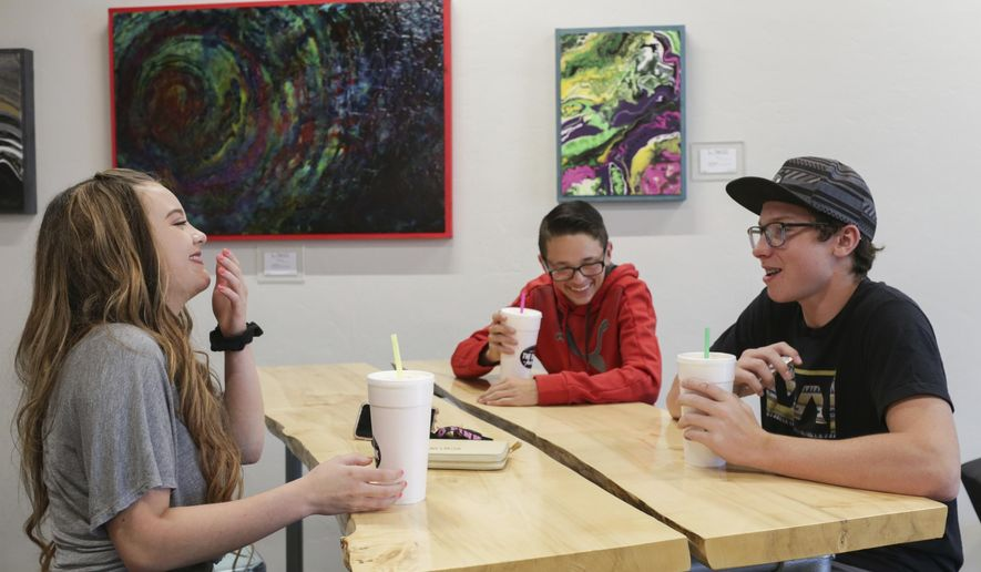 In a June 7, 2018 photo, Laurna Chapman, Landon Pinnock, with hat, and JR Chapman have sodas at The Drink Factory in Idaho Falls, Idaho.  Soda shops, also known as soda shacks, have become a mainstay in the region. (John Roark/The Idaho Post-Register via AP)