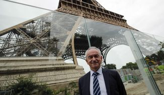 Bernard Gaudillere, president of the SETE, Eiffel Tower Exploitation Society poses in front of a new security bulletproof glass barrier under construction around the Eiffel Tower in Paris, France, Thursday, June 14, 2018. Paris authorities have started replacing the metal security fencing around the Eiffel Tower with a more visually appealing glass wall. The company operating the monument said see-through panels are being set up instead of the fences at the north and south of the famed monument that were installed for the Euro 2016 soccer event. Each panel is 3 meters high, over 6 centimeters thick and weighs 1.5 ton. (AP Photo/Francois Mori)