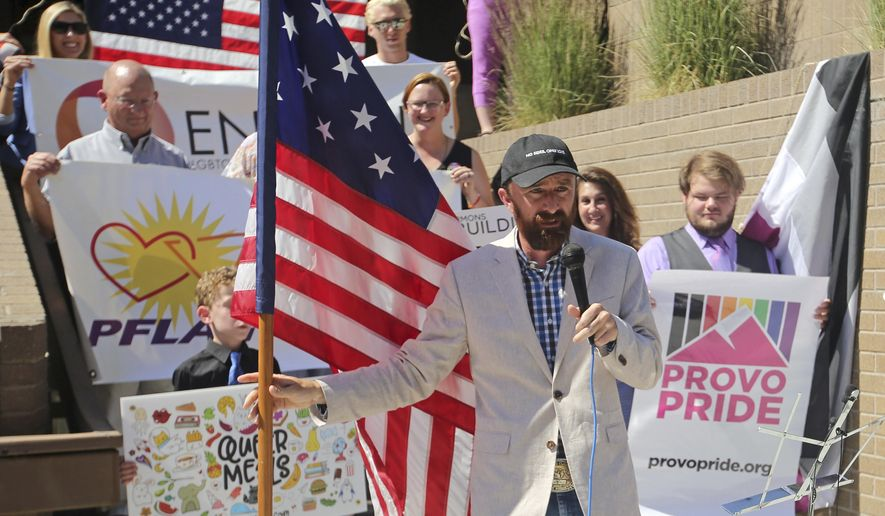 Utah County Commissioner Nathan Ivie speaks as he holds the American flag during a news conference to discuss the America's Freedom Festival's decision Thursday, June 14, 2018, in Provo, Utah. LGBT groups that were denied requests to participate in a July 4 parade that is part of America's Freedom Festival in Provo spoke out Thursday about being rejected even after festival organizer and Provo city officials signed a nondiscrimination deal. (AP Photo/Rick Bowmer)