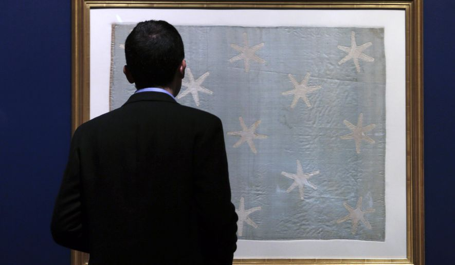 Assistant curator Matthew Skic looks the newly-hung Commander-in-Chief's Standard, Wednesday, June 13, 2018, at the Museum of the American Revolution in Philadelphia. The faded and fragile blue silk flag marked General George Washington's presence on the battlefield during the Revolutionary War. The museum is bringing the flag out of its archives for public viewing on Thursday, June 14, Flag Day, until Sunday. Its appearance at the museum is the flag's first public display in Philadelphia since the war. (AP Photo/Jacqueline Larma)