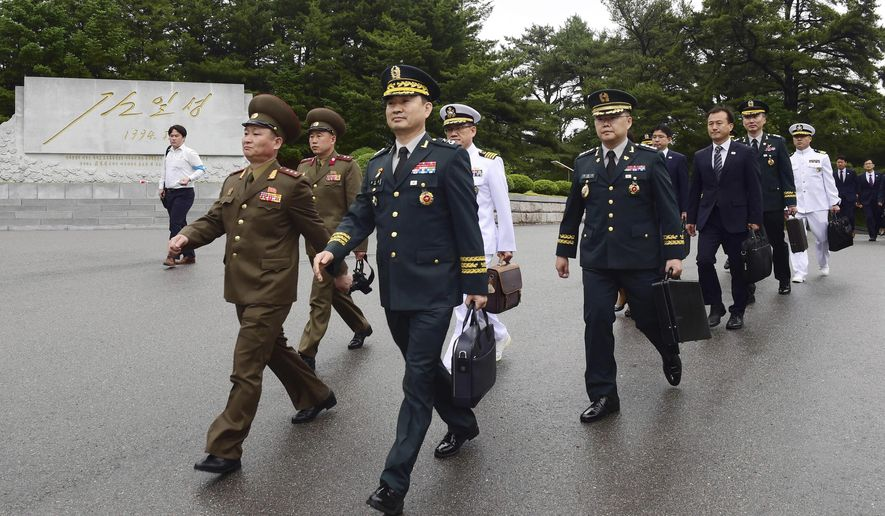 In this photo provided by the South Korea Defense Ministry, South Korean Maj. Gen. Kim Do-gyun, second from left, arrives for the meeting at the northern side of Panmunjom in the Demilitarized Zone, North Korea, Thursday, June 14, 2018. The rival Koreas were holding rare high-level military talks Thursday to discuss reducing tensions across their heavily fortified border. (South Korea Defense Ministry via AP)