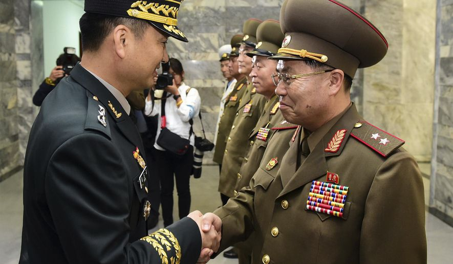In this photo provided by South Korea Defense Ministry, South Korean Maj. Gen. Kim Do-gyun, left, shakes hands with his North Korean counterpart Lt. Gen. An Ik San upon his arrival at the northern side of Panmunjom in the Demilitarized Zone, North Korea, Thursday, June 14, 2018. The rival Koreas were holding rare high-level military talks Thursday to discuss reducing tensions across their heavily fortified border. (South Korea Defense Ministry via AP).