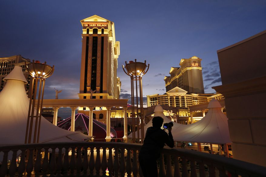 FILE - In this Jan. 12, 2015 file photo, a man takes pictures of Caesars Palace hotel and casino, in Las Vegas. Unionized workers at the casino-resorts operated by Caesars Entertainment in Las Vegas are casting ballots Thursday, June 14 to ratify their newly negotiated five-year contract.  (AP Photo/John Locher, File)