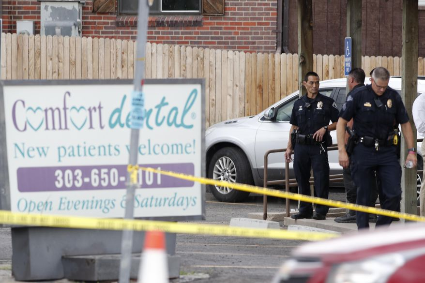 Law enforcement officials investigate the scene of a shooting in a parking lot behind Colorado's dentist's office. Thursday, June 14, 2018, in Westminster, Colo. (AP Photo/David Zalubowski)