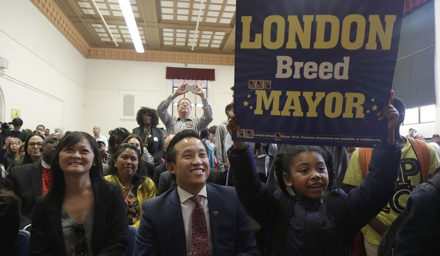 A girl holds up a sign next to California State Assembly Member David Chiu, bottom center, and Assessor Carmen Chu, bottom left, as incoming mayor London Breed speaks at Rosa Parks Elementary School in San Francisco, Thursday, June 14, 2018. It is now the job of Breed, the first black woman elected mayor of the city, to unite a wealthy but frustrated San Francisco, where the high-tech economy has sent the median price of a home soaring to $1.3 million and where homeless tents and human waste fester on sidewalks. (AP Photo/Jeff Chiu)