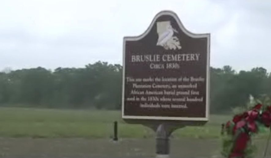In this image taken from video, a sign for Bruslie Cemetery circa 1830s stands by a burial ground for slaves in New Orleans, Wednesday, June 13, 2018. The Shell Oil Company has spruced up, marked and blocked off tracts of its land in the Convent community west of New Orleans where archaeologists confirmed the presence of slave burial grounds in 2013. (AP Photo)