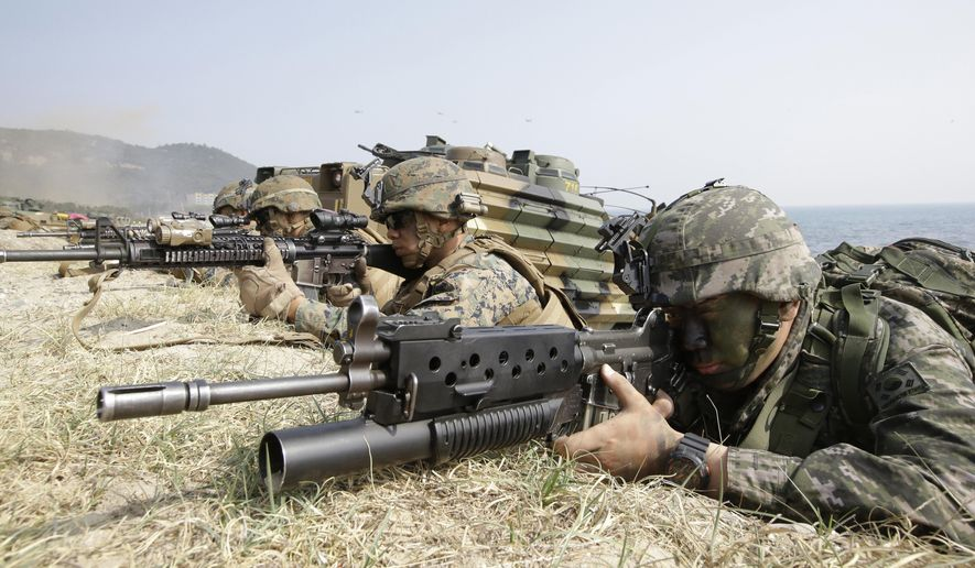 In this March 30, 2015, file photo, marines of South Korea, right, and the U.S aim their weapons near amphibious assault vehicles during U.S.-South Korea joint landing military exercises as part of the annual joint military exercise Foal Eagle between the two countries in Pohang, South Korea. (AP Photo/Lee Jin-man, File)
