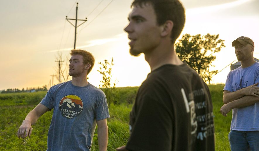 In this June 12, 2018 photo, Parker Brumm, left, Corey Johnson, center, and Jim Moore look for leftover debris in a field from Brumm's pick-up truck, in Rockford, Iowa. Johnson and Moore, volunteer firefighters with the Rockford Fire Department, were out storm watching Saturday when they witnessed an unconfirmed tornado pick up and drop Brumm's occupied truck. (Chris Zoeller/Globe-Gazette via AP)