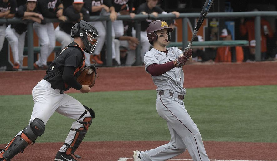 FILE - In this Friday, June 8, 2018, file photo, Minnesota's Terrin Vavra, right, reacts after striking out as Oregon State catcher Adley Rutschman, left, heads to the dugout in the first inning of an NCAA college baseball tournament super regional game in Corvallis, Ore. The number of strikeouts in college baseball is the highest on record entering the College World Series. Coaches say conditions are right for strikeouts. They say the pitching has never been better in college baseball and the focus on launch angles and exit velocities make batters more prone to striking out. (Mark Ylen/Albany Democrat-Herald via AP)