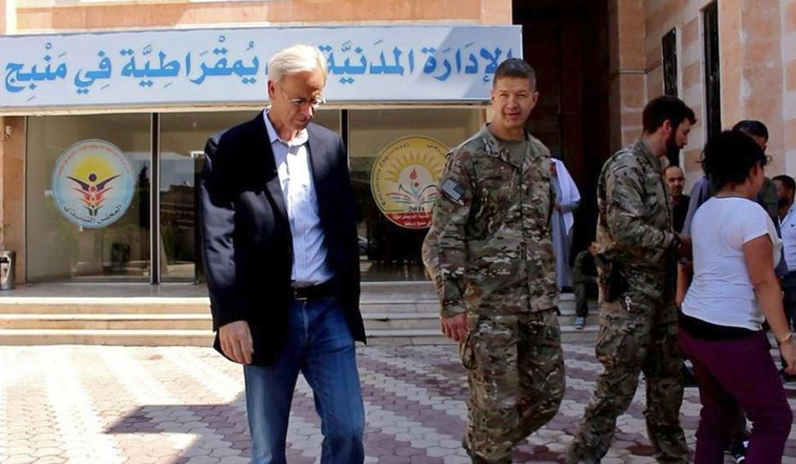 "This photo released by Hawar News, the news agency for the semi-autonomous Kurdish areas in Syria, shows the anti-IS U.S. coalition, Maj. Gen. James Jarrard, center, and veteran Middle East diplomat William Roebuck, left, in the town of Manbij, in Aleppo province, Syria, Thursday, June 7, 2018. The US delegation's visit comes days after a delicate U.S-Turkish deal that is expected to see an American-backed Kurdish militia pull out of the area. The sign in Arabic in the background reads, ""The Civil Democratic Administration in Manbij."" (Hawar News via AP)"