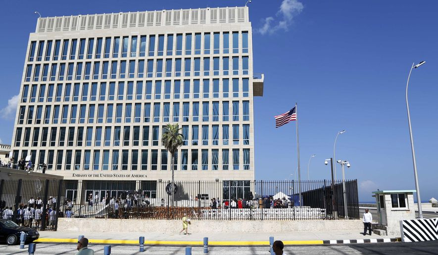 """In this Aug. 14, 2015, file photo, a U.S. flag flies at the U.S. Embassy in Havana, Cuba. The United States is renewing calls for the Cuban government to determine the source of """"attacks"""" on U.S. diplomats in Cuba that have affected some two dozen people. At a senior-level meeting with Cuban officials in Washington on June 14, 2018, the State Department said it had again raised the issue, which has prompted a significant reduction in staffing at the U.S. Embassy in Havana. (AP Photo/Desmond Boylan, File)"""