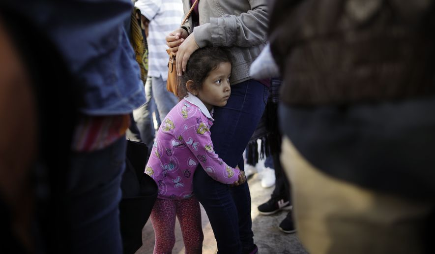 In this June 13, 2018 photo, Nicole Hernandez, of the Mexican state of Guerrero, holds on to her mother as they wait with other families to request political asylum in the United States, across the border in Tijuana, Mexico. The family has waited for about a week in this Mexican border city, hoping for a chance to escape widespread violence in their home state. (AP Photo/Gregory Bull)